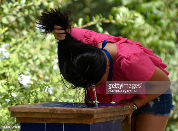A girl refreshes herself in a fountain on a hot summer day in Sevilla on August 1 2018 as a heatwave hits Spain and Portugal