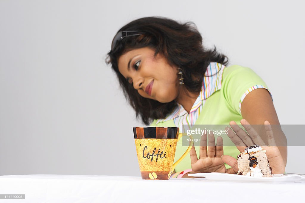 A girl refusing to eat a pastry : Stock Photo