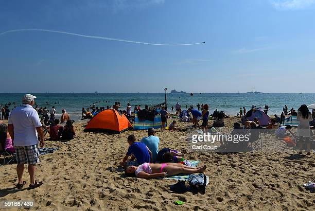 A girl relaxes with others on the beach as a plane performs a fly past during the Bournemouth Air Festival on August 18 2016 in Bournemouth England...
