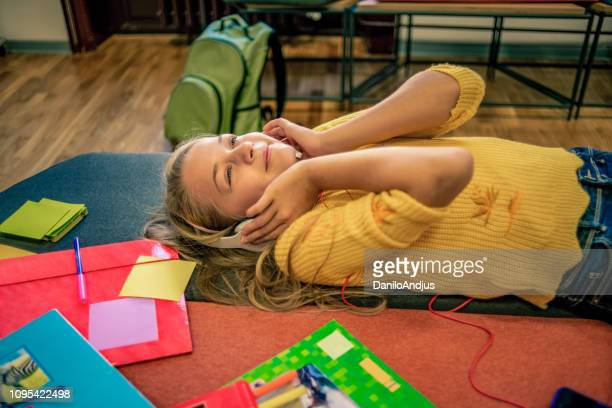 girl relaxing after class and enjoying the music - audio equipment stock pictures, royalty-free photos & images