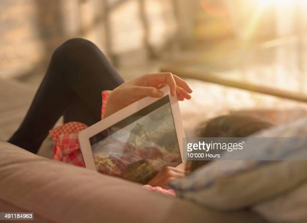 a girl relaxing at home watching a film on an tablet computer - arts culture and entertainment stock pictures, royalty-free photos & images