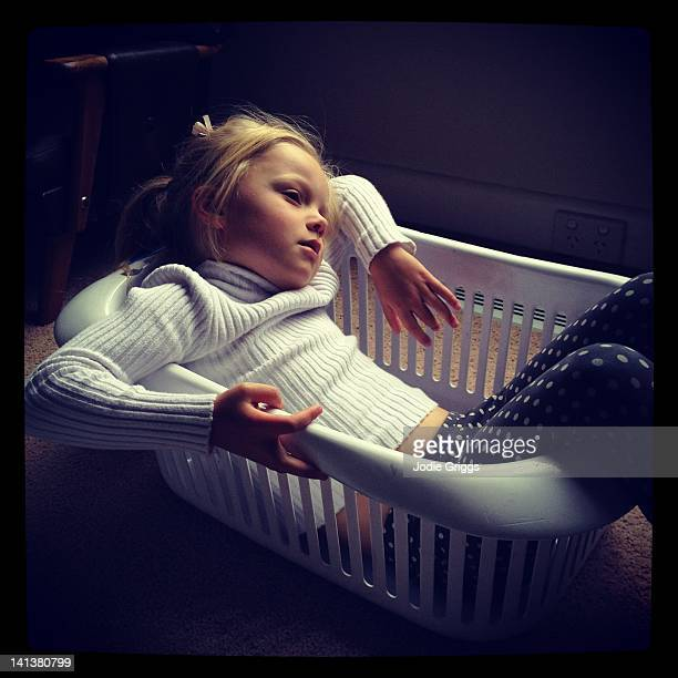 Girl relaxing in empty washing basket