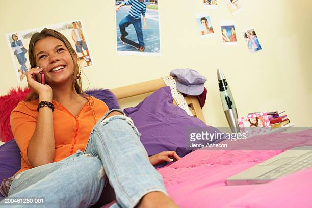 Girl (13-15) relaxing on bed using mobile phone, smiling