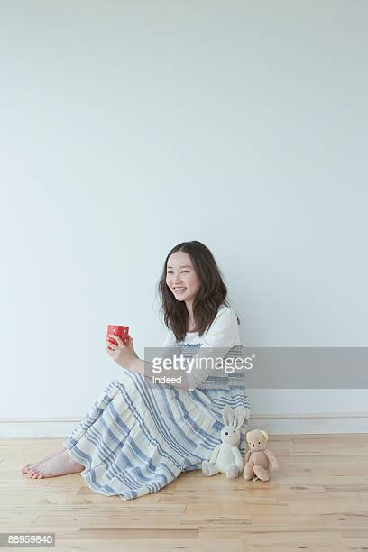 Girl relaxing on floor, holding mug, smiling