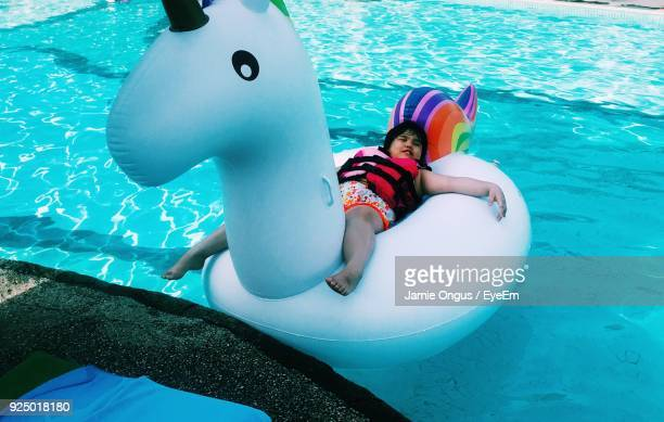 Girl Relaxing On Inflatable Duck In Swimming Pool