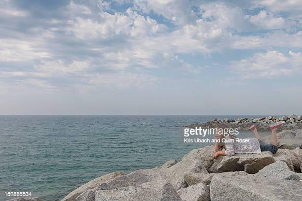 Girl relaxing on rocky beach