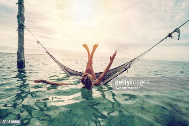 girl relaxing on sea hammock tropical climate - gili trawangan stock photos and pictures