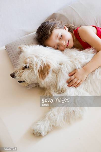 Girl relaxing with dog in bed