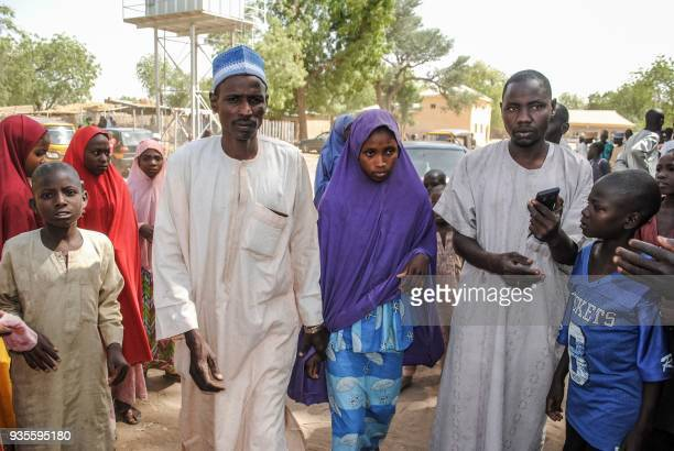 A girl released by Boko Haram walks with her father in Dapchi on March 21 2018 Boko Haram Islamists who kidnapped 110 schoolgirls in Dapchi northeast...