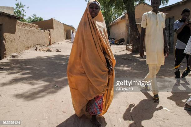 TOPSHOT A girl released by Boko Haram walks with her father in Dapchi on March 21 2018 Boko Haram Islamists who kidnapped 110 schoolgirls in Dapchi...