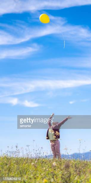 girl releasing balloon against blue sky - releasing stock pictures, royalty-free photos & images