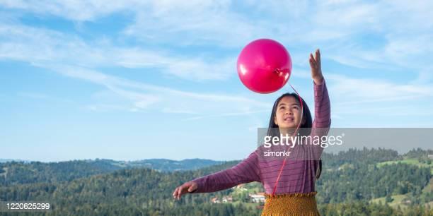 girl releasing balloon - soltar imagens e fotografias de stock