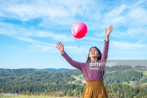 girl releasing balloon - releasing stock pictures, royalty-free photos & images