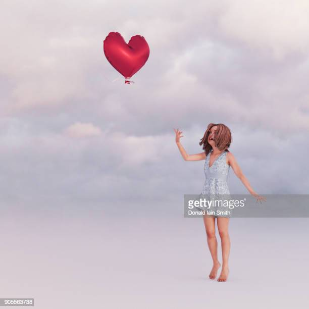 Girl releasing heart-shape balloon into sky
