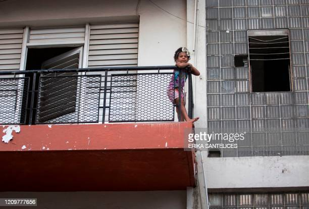A girl remains at the balcony of her home in Santo Domingo on April 12 during social isolation amid the outbreak of the new coronavirus The Dominican...