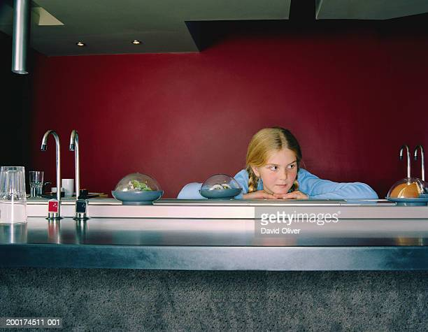 girl (10-12) resting chin on sushi bar - sushi restaurant stock photos and pictures