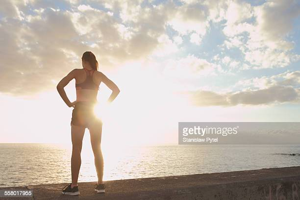Girl resting during workout near ocean, sunset