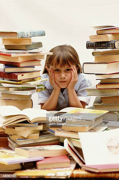 Girl (5-7) resting head in hands, surrounded by books, portrait