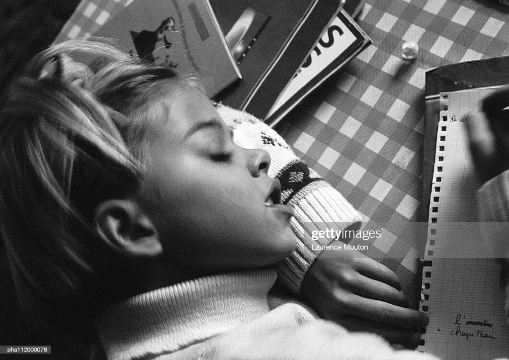 Girl resting head on arm writing, elevated view, b&w : Stockfoto