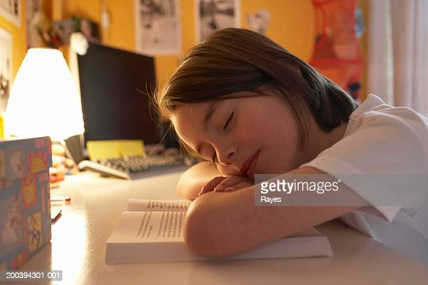 Girl (6-8) resting head on book, eyes closed, close-up
