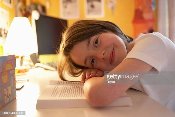 Girl (6-8) resting head on book, smiling, portrait
