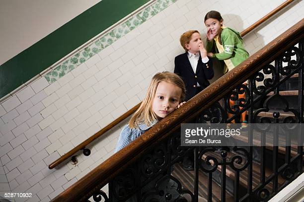 Girl Resting Head on Stair Bannister While Students Gossip Behind Her