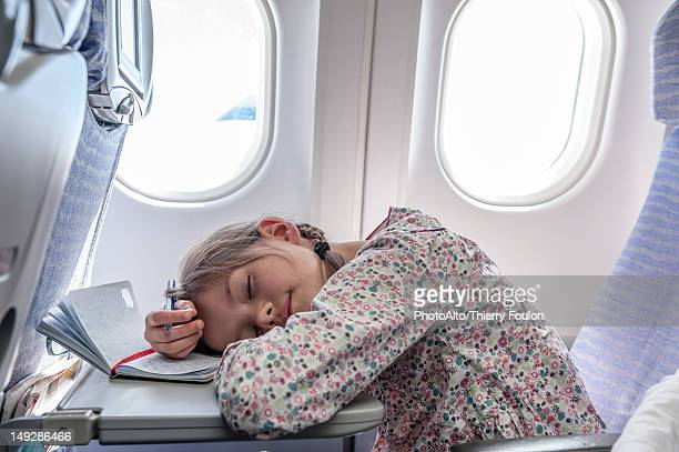 Girl resting head on tray table on airplane
