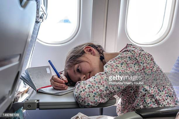 Girl resting head on tray table on airplane, writing in diary
