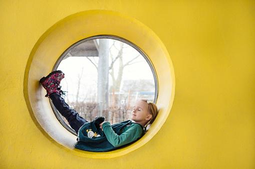 Girl (4-5) resting inside a circular window in a yellow wall - gettyimageskorea