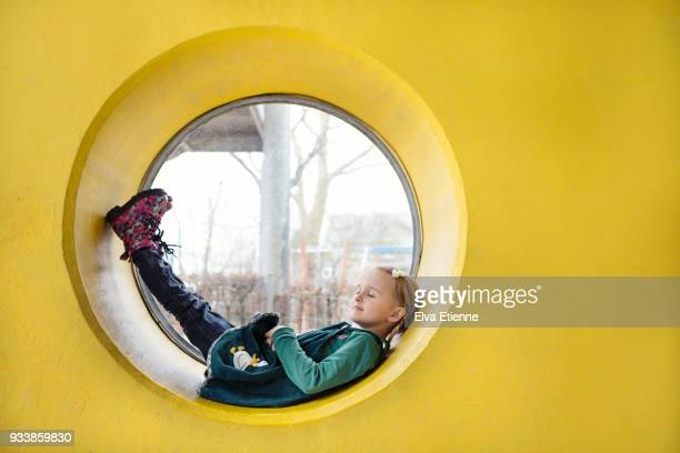 girl (4-5) resting inside a circular window in a yellow wall - circle stock pictures, royalty-free photos & images