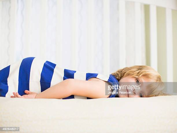 Girl (4-5) resting on bed, Los Angeles, California, USA