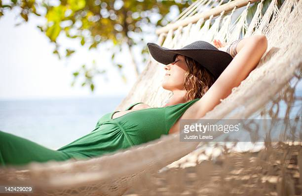 Girl resting on hammock by the beach