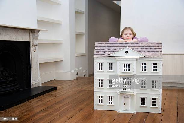 A girl resting on her dollhouse.