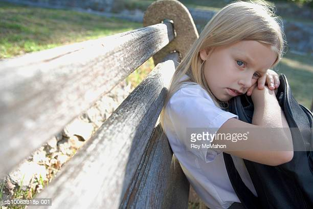 girl (8-9 years) resting on school bag, sitting on park bench - 8 9 years stock pictures, royalty-free photos & images