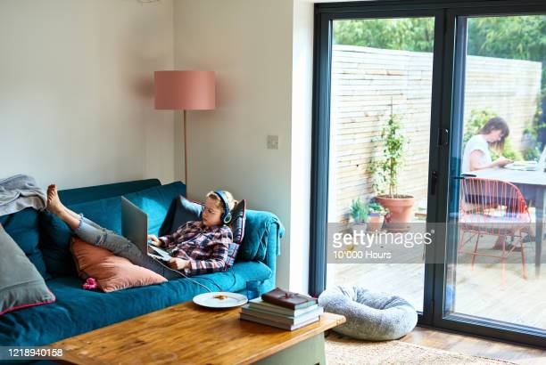 girl resting on sofa with laptop during lockdown - stream stock pictures, royalty-free photos & images