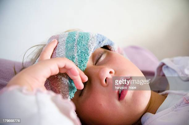 Girl resting with a wet towel on her forehead