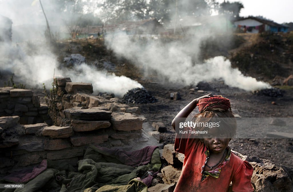 A girl rests as smoke rises from burning coal in Bokapahari in Dhanbad, Jharkhand, India on December 6, 2014. Indian government lead by Prime Minister Narendra Modi plans to double its coal production by 2019.