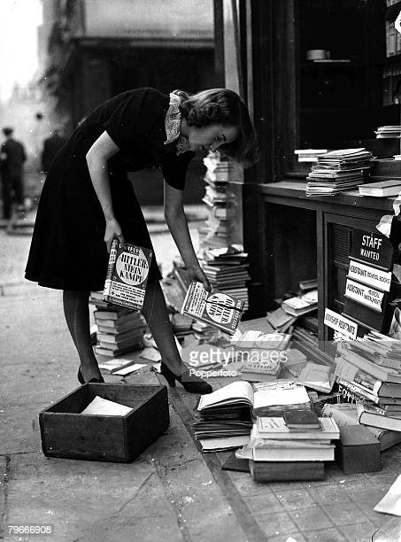 A girl retrieves copies of Adolf Hitler's book Mein Kampf when the front of the London bookshop was blown out by the explosion of a German bomb 1940