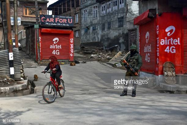 A girl rides a bicycle as Indian policeman stands guard during curfew in Srinagar Indian administered Kashmir As Muslim majority areas of Kashmir...