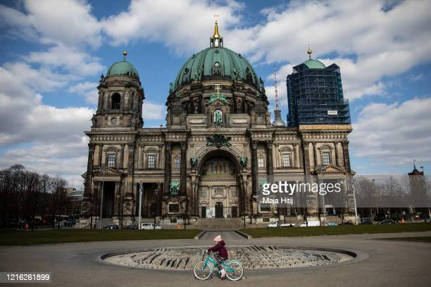 Girl rides a bike near Berlin Cathedral during the coronavirus crisis on April 01, 2020 in Berlin, Germany. The coronavirus and the disease it...