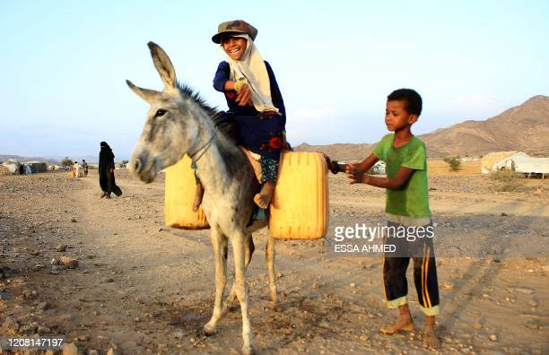 Girl rides a donkey carrying jerry cans filled with water from a cistern at a make-shift camp for displaced Yemenis in severe shortage of water, in...