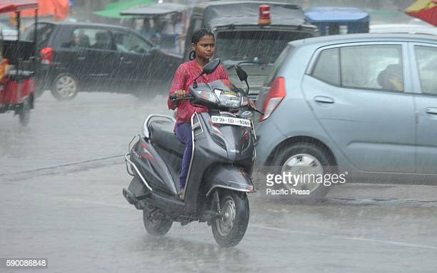 A girl rides a scooter during heavy rain in Allahabad