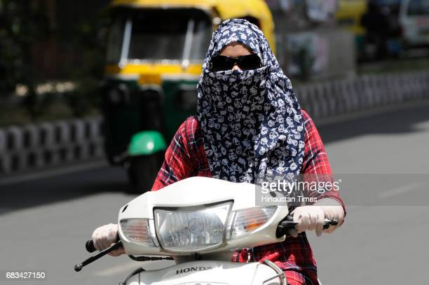 A girl rides a scooty on a hot summer day on May 15 2017 in New Delhi India Heat wave conditions prevailed in the capital as mercury crossed 43...