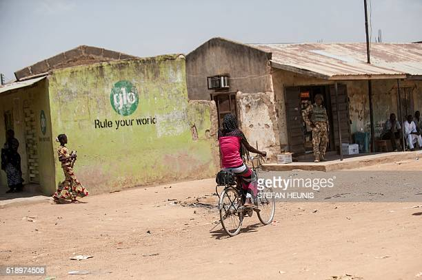 A girl rides her bicycle down a street of Chibok in Borno State northeastern Nigeria on March 25 2016 There's not much left of the Government Girls...