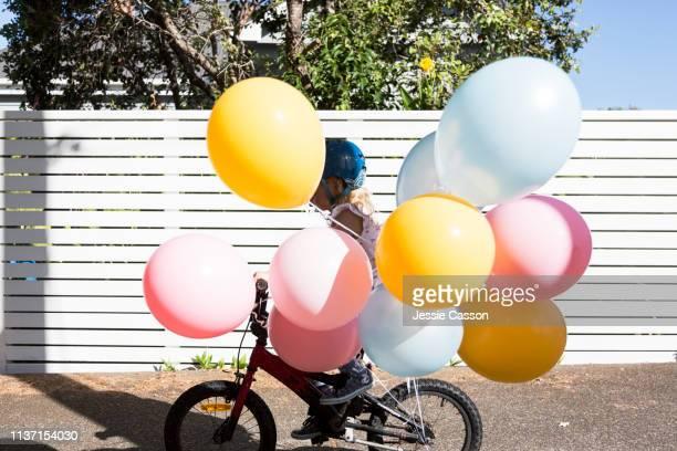 a girl rides her bike with colourful balloons - verdecktes gesicht stock-fotos und bilder