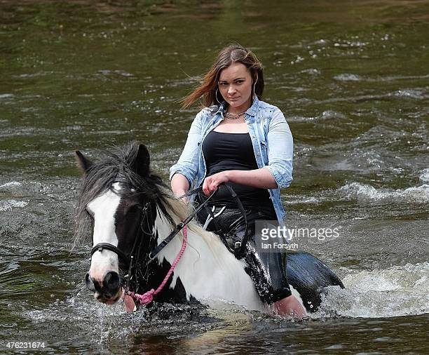 A girl rides her horse through the River Eden during the Appleby Horse Fair on June 7 2015 in Appleby England The fair is an annual gathering for...