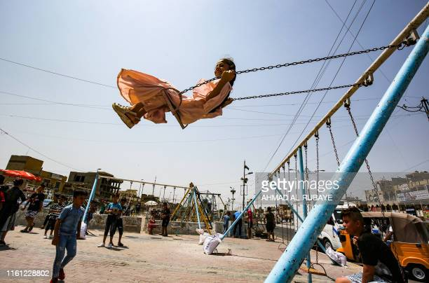 A girl rides on a swing in the Iraqi capital Baghdad's eastern suburb of Sadr City as people celebrate the Muslim religious festival of Eid alAdha on...