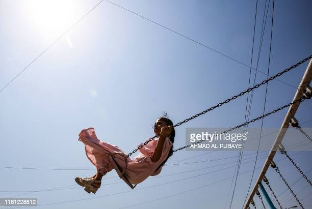 TOPSHOT A girl rides on a swing in the Iraqi capital Baghdad's eastern suburb of Sadr City as people celebrate the Muslim religious festival of Eid...