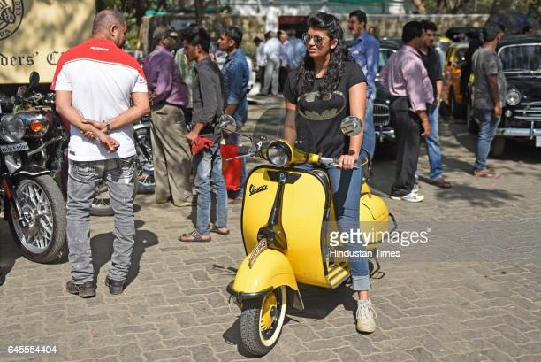 A girl rides on a yellow colour Vespa during the display and inspection of Vintage Cars at Mahalaxmi Race Course on February 25 2017 in Mumbai India
