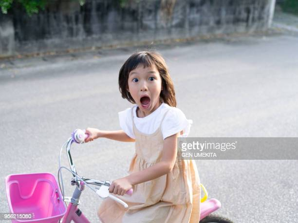 a girl riding a bicycle - seven crash stock pictures, royalty-free photos & images